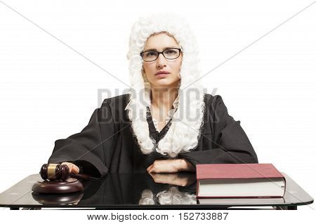 Female judge wearing a wig and Back mantle with eyeglasses with judge gavel and book isolated on white backgriund