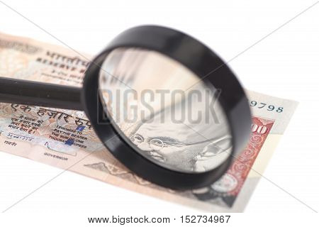 Indian Currency Rupee Note with magnifying glass isolated on white background