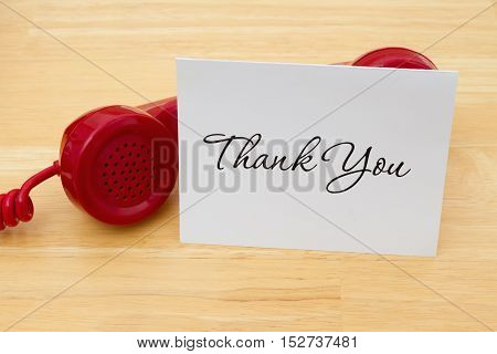 Getting a call to say thanks A retro red phone with greeting card on a desk with text Thank You