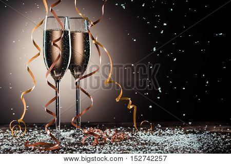 Romantic image of two glasses with sparkling champagne and ribbons