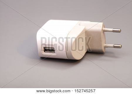Electrical adapter to USB port on a gray background