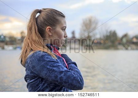 A young woman exercises by the river