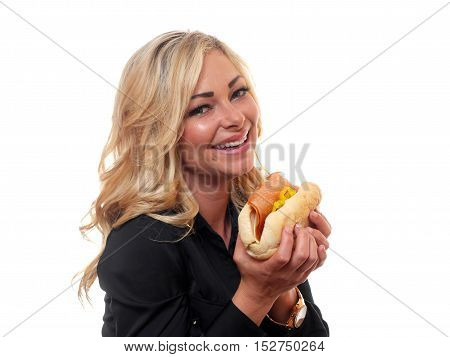 A attractive woman is eating a deli style sandwich.