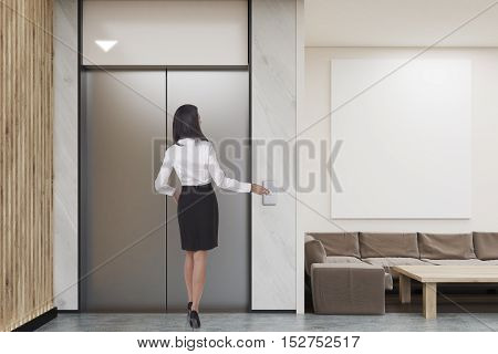 Woman waiting for the elevator in company lobby with vertical poster coffee table sofa and elevator. Concept of modern waiting area design. 3d rendering. Mock up.