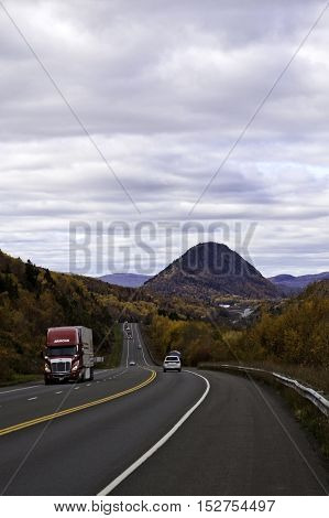 Cambellton NB, October 17, 2016 -- Vertical shot looking down Highway 11 into Cambellton, NB with a view of the small mountain the town is bordered by, on a slightly overcast but bright day in October. Cambellton borders Sugarloaf Provincial Park and has