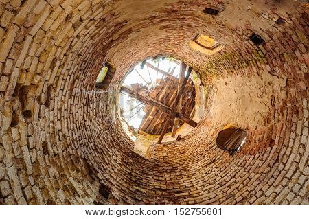 The Inside Bottom View Of Destroyed Abandoned Brick Through Tower In Evacuated Zone After Chernobyl Catastrophe. Consequences Of The Nuclear Contamination