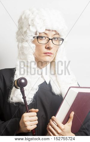 Female judge wearing a wig and Back mantle with eyeglasses holding judge gavel and book on white backgriund