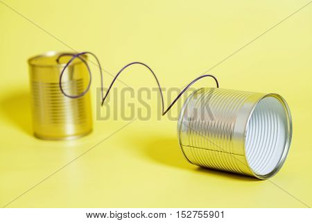tin can phone on a yellow background.communication concept
