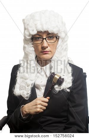 Female judge wearing a wig and Back mantle with eyeglasses holding judge gavel isolated on white backgriund