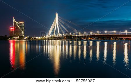 Riga, Latvia - July 01, 2016: The Scenic View Of Vansu Cable-Stayed Bridge In Bright Evening Illumination Over The Daugava River, Western Dvina And Color Reflexions On Water Surface. Central Building  Swedbank at evening.