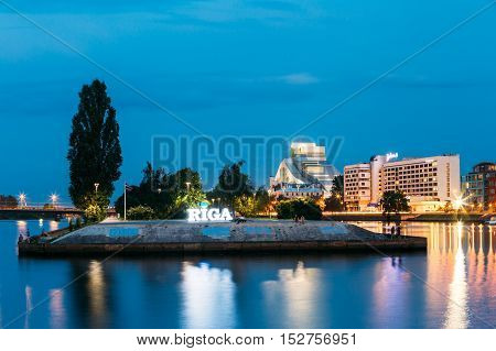 Riga, Latvia - June 30, 2016: The Scenic Cityscape In Evening Illumination. View Of Urban Embankment Of Daugava River,  Glowing City Name Sign In Summer Dusk.