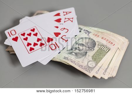 Royal Flush Playing Cards and Indian Currency Rupee bank notes isolated on gray background