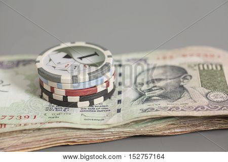 Poker chips on Indian Currency Rupee bank notes on gray background