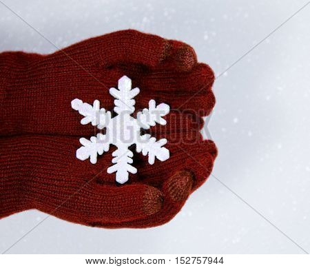 Close up of hands in red gloves holding a plastic snowflake for winter or Christmas