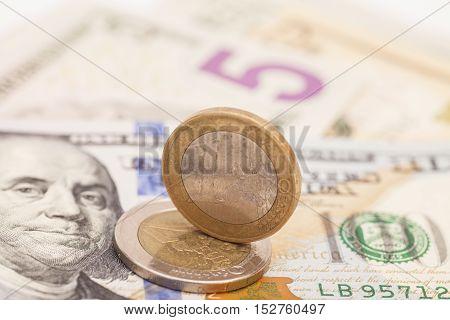 Euro coins over dollar US notes money.