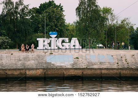 Riga, Latvia - June 30, 2016: Three Young Women Sitting On The Edge Of Concrete Embankment Of Daugava River Next To Big Sign Of City Name.