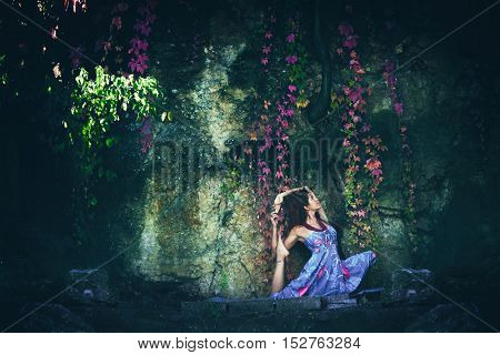 young woman practice yoga outdoor shot in front of rock with autumn leaves