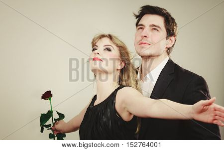 Love in air. Freedom of feelings. Charming gorgeous couple wearing elegant clothes in gust of wind. Enamoured fabulous woman and man making titanic gesture. poster