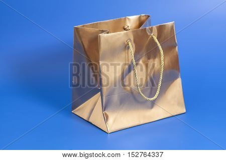 Golden package for gift on blue background
