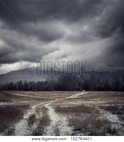 Dark Gloomy Landscape with Country Road in Snow. Moody Sky Background with Epic Dramatic Clouds around Mountains. Cold Winter Fantasy Scenery. Toned HDR Styled Photo.