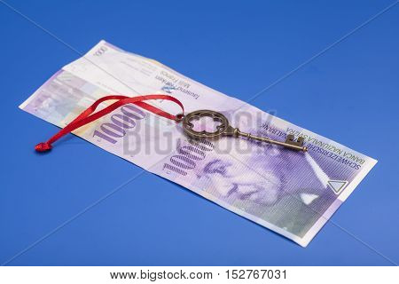 Key To Success With Red Bow on 1000 Swiss Franc note on blue