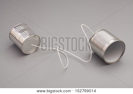 tin can phone on gray background. communication concept