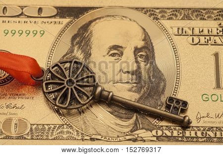 Key To Success With Red Bow on Golden hundred dollar bill
