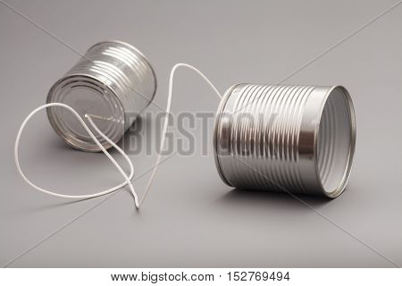 tin can phone on a grey background. communication concept