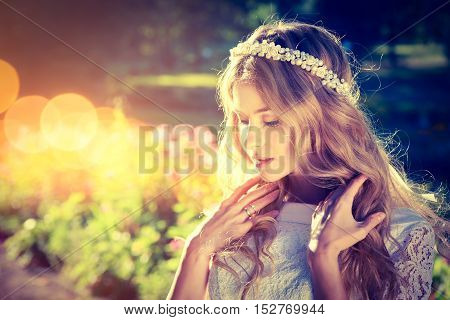 Romantic Bride with Wedding Tiara on Warm Nature Background. Modern Bridal Style. Candid Image. Toned Photo with Bokeh and Copy Space.