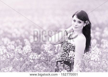 Pretty summer girl posing in pink meadow of flowers. Attractive happy young girl enjoying the warm summer sun and her health in a wide green and yellow meadow. Part of series.