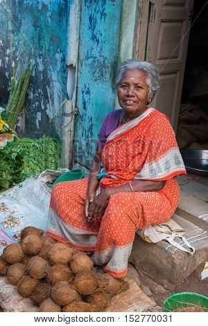 Madurai India - October 22 2013: An older graying woman in red sari sells a handful of coconuts sitting on her doorstep. Blue wall.