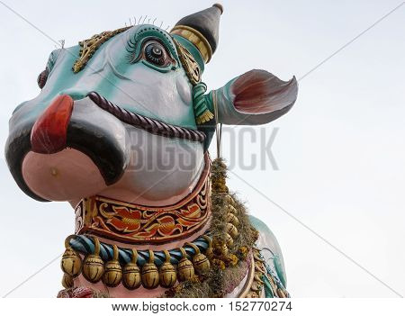 Madurai India - October 22 2013: In front of the Meenakshi temple in town stands this giant colorful statue of Nandi the bull. Close up of his head and neck only. Garlands of bells.