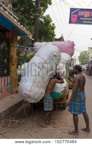 Madurai India - October 22 2013: Huge cotton bales are unloaded from a small truck in a downtown street early in the morning. One man carries a huge bale on his back while another man looks on.