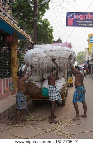 Madurai India - October 22 2013: Three half-naked men unload huge cotton bales from a small truck. Two men are helping the third man to put the bale on his back.