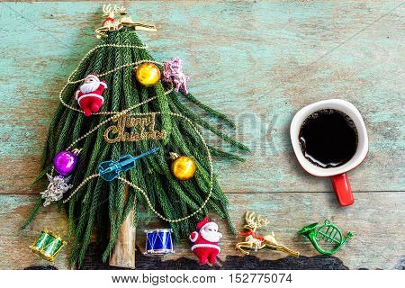Decorated Christmas tree and cup of coffee on wooden background