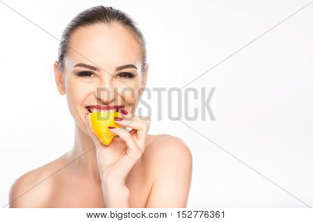 Healthy young woman is biting lemon with enjoyment. She is standing and smiling. Isolated and copy space in right side