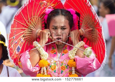 Phuket Town, THAILAND, October 07, 2016 : Female devotee extreme piercing street procession during the Taoist vegetarian festival of the Nine Emperor Gods in Phuket, Thailand .