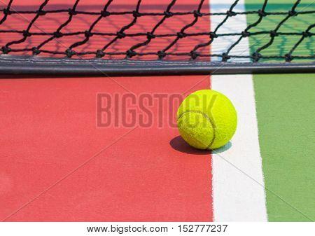 Tennis ball on green tennis court and net