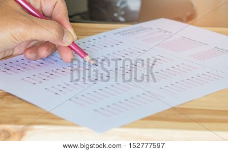 Blurred of Thai student writing a test in exercise exams test paper answer sheet with hands : education concept