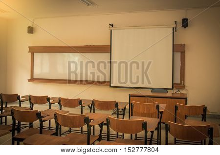 University classroom with desks blackboard and screen projecter in thailand university
