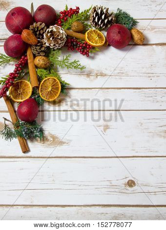 Christmas Potpourri background with oranges dried fruit cinnamon sticks nuts with room for Copy Space on wood plank board