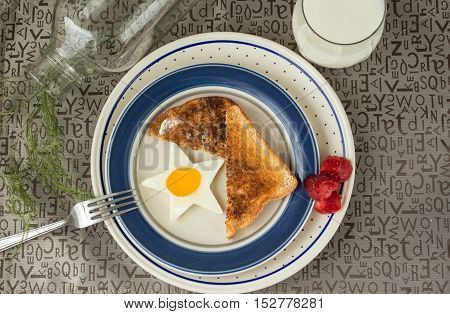 horizontal image of a breakfast set up of a star shaped fried egg with toast and strawberries on the side in a blue rimmed plate with a glass of milk on brown textured background.