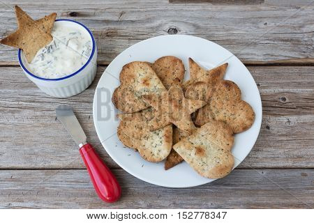 horizontal image of a plate of home made freshly baked  crispy tortilla chips with a bowl of spinach dip on the side with a little knife on a rustic wood background.