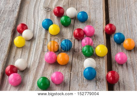 horizontal image of different coloured bubble gum scattered on an old rustic wooden background