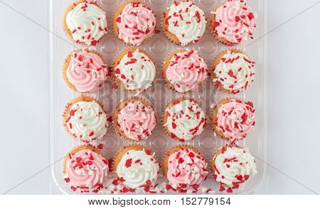 horizontal image of a group of muffins with white and pink icing with little red valentine candy sprinkles isolated on white background with room for text.