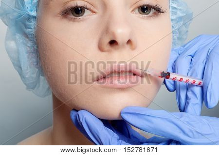 Attractive young woman gets cosmetic injection an injection in the upper lip over blue background. Doctors hands making an injection in face close-up. Beauty Treatment. shot in the upper lip