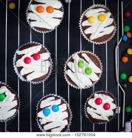 Funny idea for Halloween dessert - cute mummy cupcakes on a black wood background top view blank space for text Halloween. children's holiday. Chocolate cupcakes colored eyes m&ms. Food for Halloween.