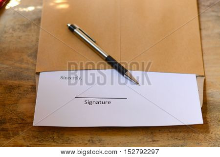 Pen and paper are placed in the working document for a signature.