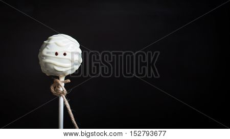 Cake Pop mummy. Original card for Halloween. Copy Space. Funny idea for Halloween dessert. Black wood background top view blank space for text Halloween. Halloween