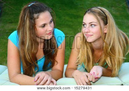 Teenage girls outside, talking.